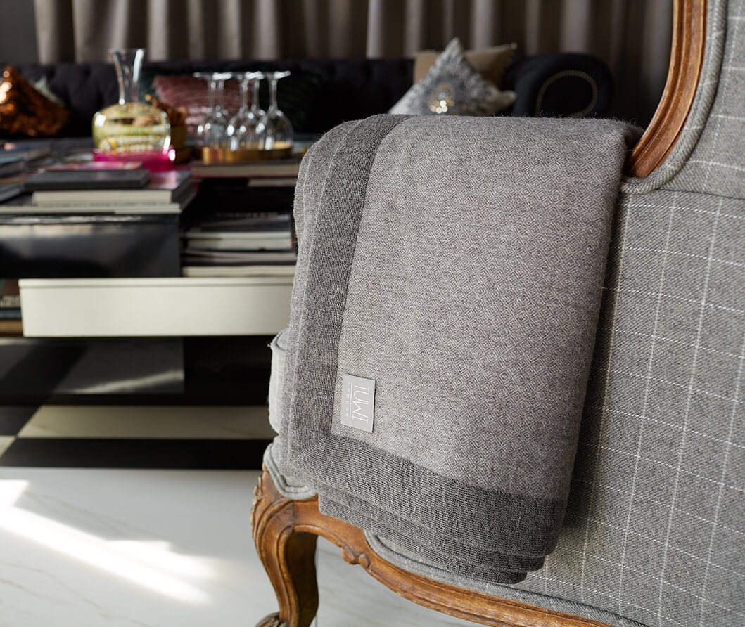 Tuwi Roca Throw taupe draped over grey armchair