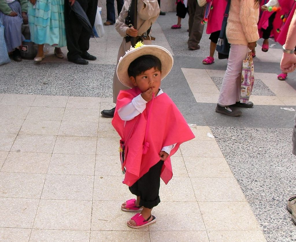 Peruvian Child Standing In A Crowd Wearing A Pink Poncho and straw hat