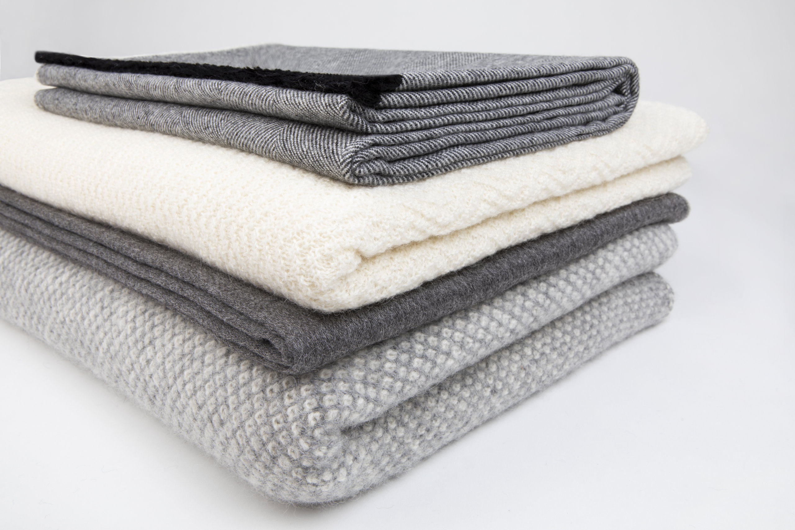 A pile of beautiful alpaca throws in neutral shades from Tuwi London