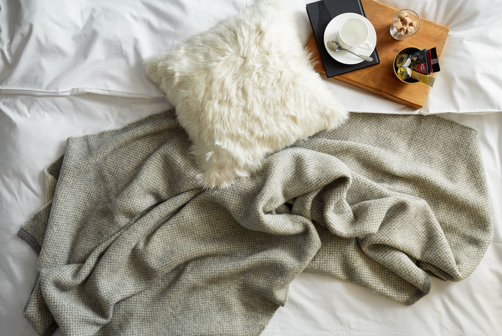 Baby alpaca throw and cushion on bed, from Tuwi London